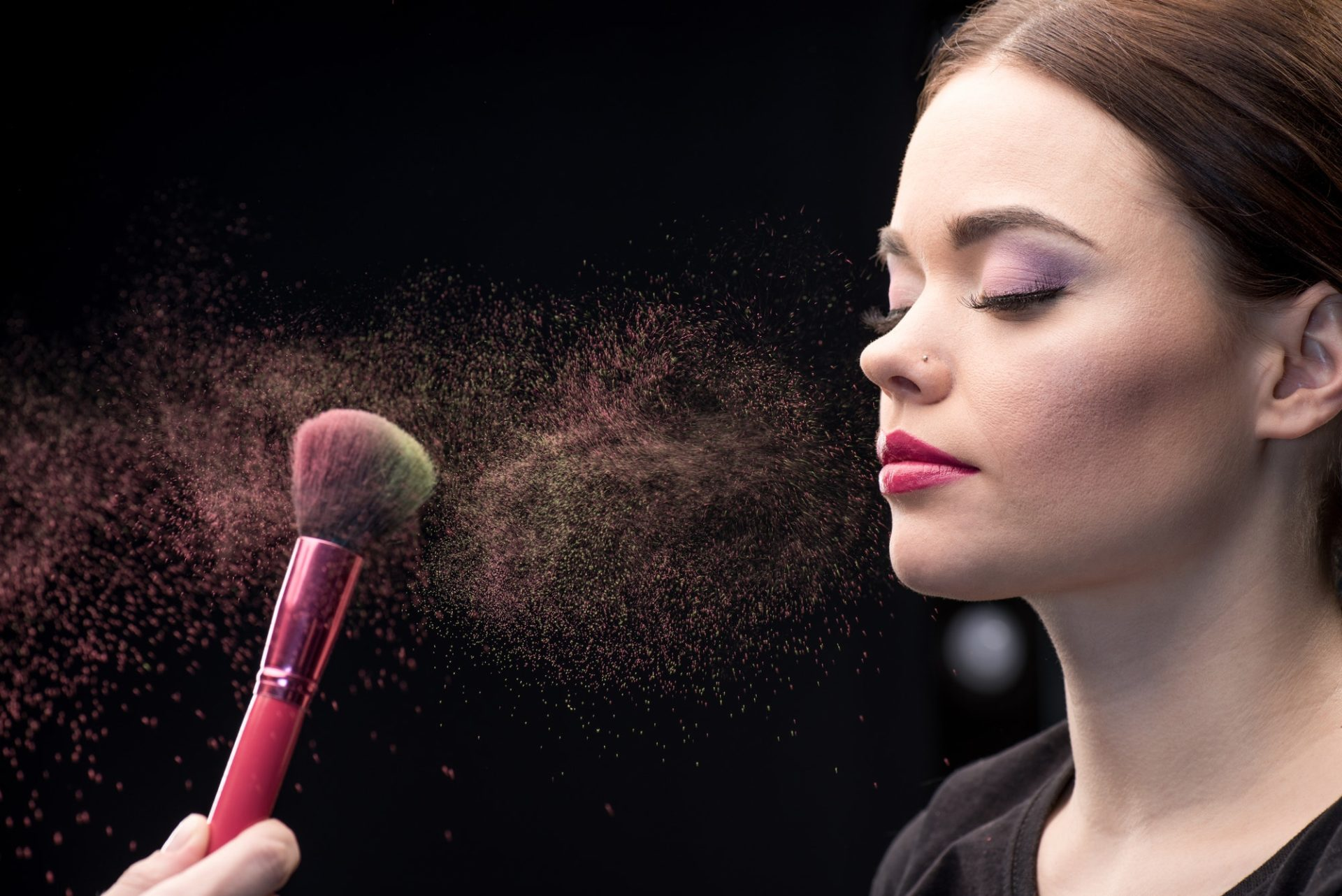 make-up-artist-sprinkling-model-s-face-with-powder-with-help-of-brush-on-black.jpg